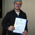 Steen Fredrickson holds up his signed National Letter of Intent to play baseball at Montana State University Billings